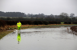 © London News Pictures. 06/01/2016. A council worker walks through a road flooded on Berwick Hill, Ponteland, North east England. Large parts of the UK continue to suffer flooding after more heavy rain.  Areas of Northumberland and the North East have suffered with many being displaced from their homes as a result of flooding. Photo credit: Adam Davies/LNP