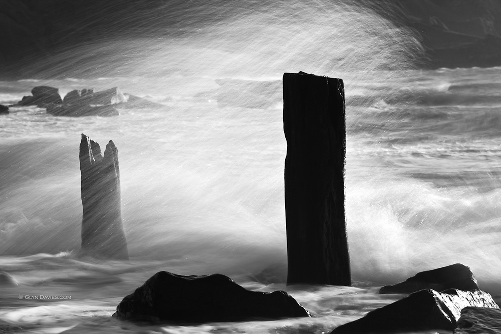 """""""Two of the last few stumps of the cargo jetties stand defiantly against the continual battering of the sea, the last tiny reminders of the link with the sea, from an industry long gone and a community dispersed""""<br /> <br /> From my book<br /> <br /> """"Nant Gwrtheyrn - Y Swyngyfaredd (The Enchantment)"""" available here on my website<br /> <br /> The deserted valley and quarrying village of Nant Gwrtheyrn, North Wales. Now restored as a Welsh language & conference centre."""