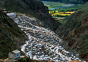 """Since pre-Inca times, salt farmers at the saltworks (salinas) near Maras have evaporated salty water from a subterranean stream in Peru, South America. A rough dirt road connects Maras (in the Urubamba/Vilcanota River Valley, Sacred Valley of the Incas) with Cuzco (40 km north) and other towns. The cooperative system of pond farmers was established during the time of the Incas, if not earlier, and is traditionally available to any person wishing to harvest salt. Intricate channels redirect water flow through several hundred ancient terraced ponds. As water evaporates from the sun-warmed ponds, it becomes supersaturated and salt precipitates as crystals. A pond keeper closes the water-feeder notch, allows the pond to go dry, then scrapes and carries away the dry salt. Salt color varies from white to a light reddish or brownish tan, depending on """"farmer"""" skills."""