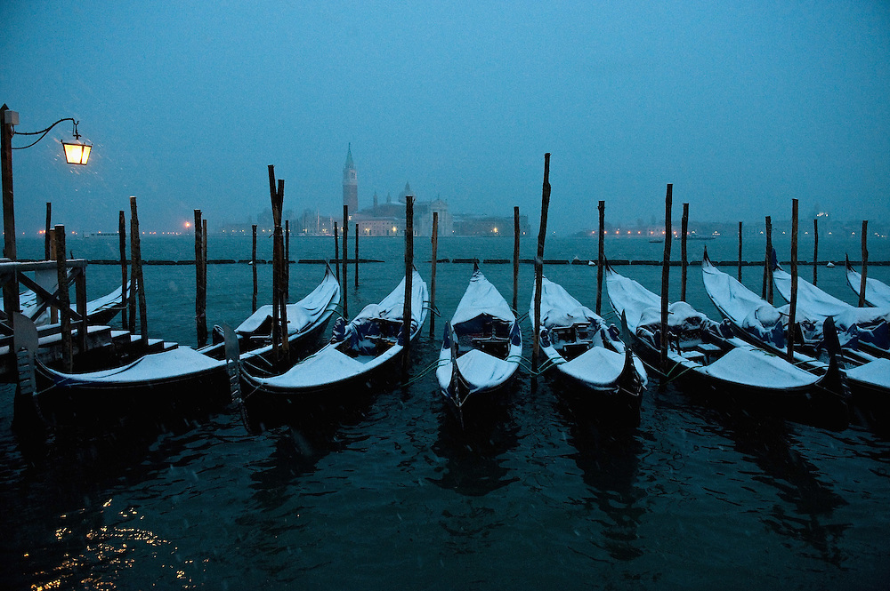 VENICE, ITALY - DECEMBER 17:  Gondolas covered with snow in San Marco on December 17, 2010 in Venice, Italy. Snow has fallen across much of Europe today and is expected to continue over the weekend, causing traffic chaos and disrupting Christmas deliveries. Doge Palace is the former Doge's residence and the seat of Venetian government, the Palace is the very symbol of Venice and a masterpiece of Gothic architecture.