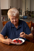 Senior woman eating berries for a snack.