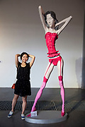 Contemporary art sculpture of a woman with thin limbs and wearing shocking pink underwear generates a lot of interest with art lovers at a gallery in 798.  798 Art Zone or Dashanzi Art District, is a part of Dashanzi in the Chaoyang District of Beijing, China that houses a thriving artistic community, among 50-year old decommissioned military factory buildings of unique architectural style. The area is often called the 798 Art District or Factory 798 although technically, Factory #798 is only one of several structures within a complex formerly known as Joint Factory 718.