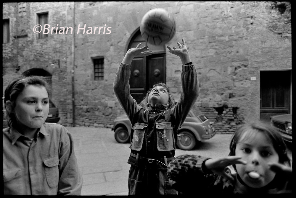 Casole d'Elsa, Tuscany, Italy. 1990. Scanned in 2019<br />Children play in the streets of Casole.<br />Street and cafe bar life in the small hill top town of Casole d'Elsa in Tuscany Italy