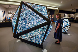 """© Licensed to London News Pictures. 25/06/2019. LONDON, UK. A staff member views """" 80'' Icosahedron """", 2019, by Anthony James from Opera Gallery for the Sculpture Series at a preview of Masterpiece London 2019, the world's leading cross-collecting art fair held in the grounds of the Royal Hospital Chelsea.  The fair brings together 157 international exhibitors presenting works from antiquity to the present day and runs 27 June to 3 July 2019.  Photo credit: Stephen Chung/LNP"""