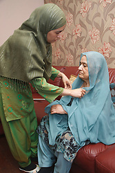 South Asian woman helping her mother with her hijab.