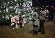 Newburgh, New York- Children pose for photographs in front of the tree after the Christmas tree lighting ceremony on Broadway on the night of Dec. 14, 2011.