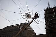Workmen on a cherry-picker making adjustments to Web of Light by the Chinese-born artist Ai Weiwei which features a giant spider in its web suspended from buildings in Exchange Flags in the centre of Liverpool. The installation, made of light tubes and glass beads, is part of the 2008 Liverpool Biennial, the UK's largest contemporary international arts festival which commences on September 20 and runs until the end of November. Liverpool was also 2008 European Capital of Culture.
