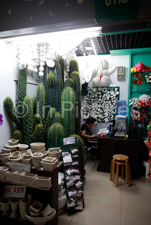 A woman sits in her stall selling plastic cacti at the Yiwu International Trade City in Yiwu, Zhejiang Province, China on Sunday, 11 September 2011.   As the trading hub for small and medium manufacturers and exporters in the Yangtze River Delta region, Yiwu faces an uncertain future as export orders decline due to the slow economic recoveries of China's two largest trading partners, Europe and the United States