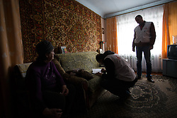 Siminova Nadiersha receives a visit from Doctor Khachatur Malakyan (c) and nurse Andrei Bogma (r) during an MSF home visit to check her blood sugar levels and deliver medecines to her. Siminova lives alone in Dabelsevo, suffering from hyper tension and diabetes. and is only able to make it outside in her immediate neighbourhood, she cannot walk far . Since the conflict in their city residents rely on humanitarian assistance in the form of food distributions and medical treatment due to shortages and lack of drugs and medical professionals in the town., suffering from hyper tension and diabetes. She is only able to make it outside in her immediate neighbourhood and cannot walk far . Since the war in their city residents rely on humanitarian assistance in the form of food distributions and medical treatment due to shortages and lack of drugs and medical professionals in the town.