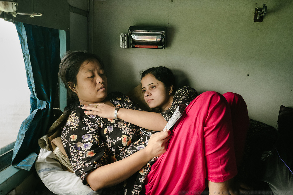 Two friends that met during the train ride embrace while laying on the bed.<br /> Inside the Dibrugarh-Kanyakumari Vivek Express, the longest train route in the Indian Subcontinent. It joins Kanyakumari, Tamil Nadu, which is the southernmost tip of mainland India to Dibrugarh in Assam province, near the border with Burma.