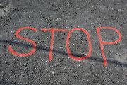 The word STOP sprayed on to a road surface, on 21st June 2018, in Kobarid, Slovenia.