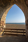 Stone arch of old lime kilns on Holy Island,  Northumberland, England, UK view south of coastline