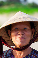 Smiling woman wearing a traditional conical hat on China Beach in Vietnam.