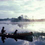 Canoeist fishing with lab in canoe on small northern Minnesota lake. Early morning.  Northern Minnesota.