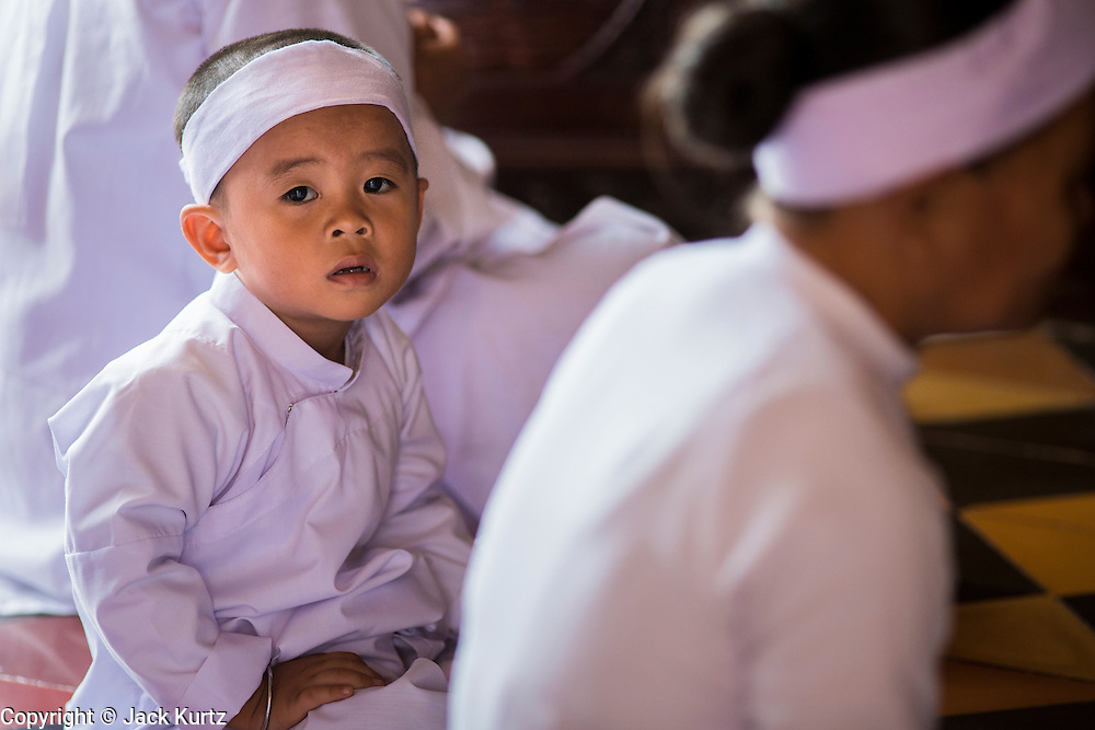 """29 MARCH 2012 - TAY NINH, VIETNAM:   Cao Dai adherents, in white, during noon services at the Cao Dai Holy See in Tay Ninh, Vietnam. Cao Dai (also Caodaiism) is a syncretistic, monotheistic religion, officially established in the city of Tây Ninh, southern Vietnam in 1926. Cao means """"high"""" and """"Dai"""" means """"dais"""" (as in a platform or altar raised above the surrounding level to give prominence to the person on it). Estimates of Cao Dai adherents in Vietnam vary, but most sources give two to three million, but there may be up to six million. An additional 30,000 Vietnamese exiles, in the United States, Europe, and Australia are Cao Dai followers. During the Vietnam's wars from 1945-1975, members of Cao Dai were active in political and military struggles, both against French colonial forces and Prime Minister Ngo Dinh Diem of South Vietnam. Their opposition to the communist forces until 1975 was a factor in their repression after the fall of Saigon in 1975, when the incoming communist government proscribed the practice of Cao Dai. In 1997, the Cao Dai was granted legal recognition. Cao Dai's pantheon of saints includes such diverse figures as the Buddha, Confucius, Jesus Christ, Muhammad, Pericles, Julius Caesar, Joan of Arc, Victor Hugo, and the Chinese revolutionary leader Sun Yat-sen. These are honored at Cao Dai temples, along with ancestors.    PHOTO BY JACK KURTZ"""