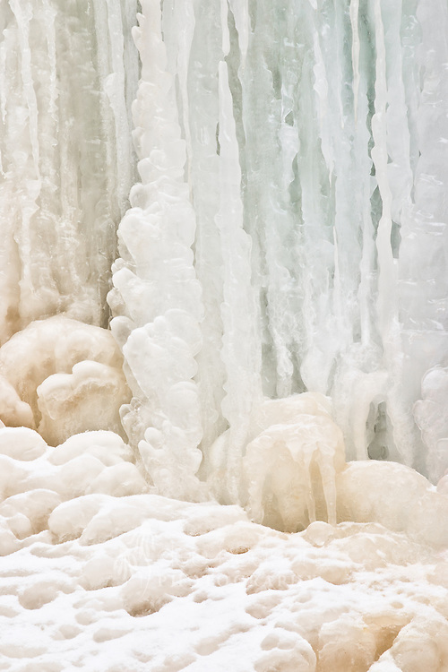 Colors and design are captured in the frozen ice below a waterfall.