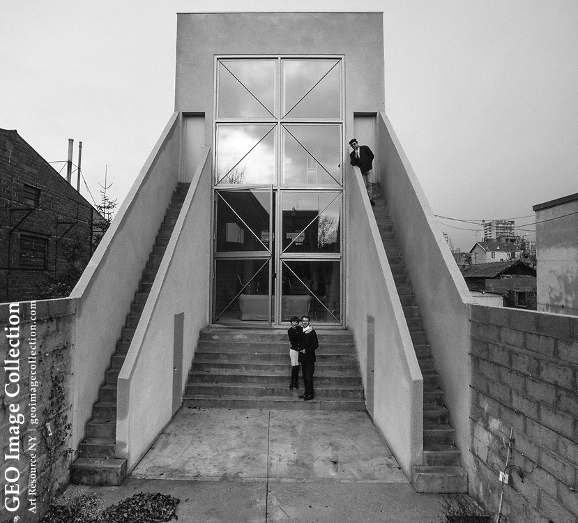 Maison Le Moult, a glass and concrete home designed by Philippe Starck in a Parisian suburb, with first owners Bruno Le Moult and Madame. Mr. Starck stands on the right staircase. The 1987 house was named for its first owner, the late Bruno Le Moult, a prominent French advertising executive. Mr. Le Moult, a friend of Mr. Starck's, worked at the advertising agency CLM BBDO when the house was built. The structure is on an island in the Seine River.