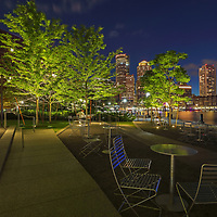 Boston Harbor skyline and fan pier outdoor seating and city living photographed Greater Boston area photographer Juergen Roth. The digital photography image shows outdoor space where Bostonians and travelers can hang out on a Saturday night with the famous Boston Financial Waterfront District landmarks such as One International Place, Boston Harbor Hotel, Independence Wharf, Department of Homeland Security building in the backdrop.<br />