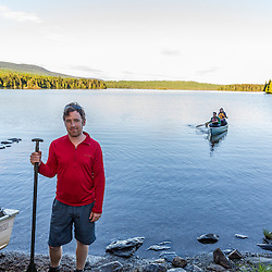 A man waits on shore while a couple paddles their canoe in from a morning excusion on Long Pond in Maine's north woods. Near Greenville, Maine.