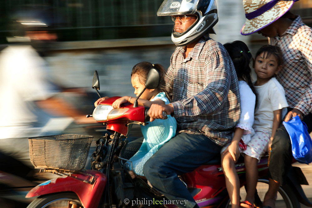 A family ride on one motorcycle in the busy streets of Siem Reap, Cambodia