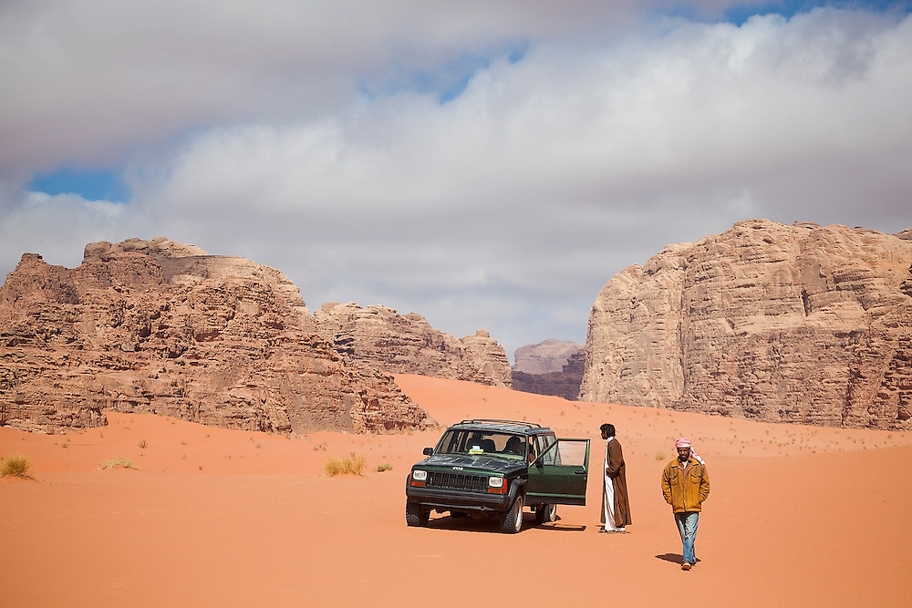 Bedouin men (with a broken down jeep) ask for help from a passing jeep in the desert in Wadi Rum, Jordan.