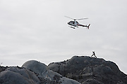 Adam LeWinter, of the Extreme Ice Survey, runs to meet a helicopter coming in for landing at the research camp at the Columbia Glacier, near Valdez, Alaska.