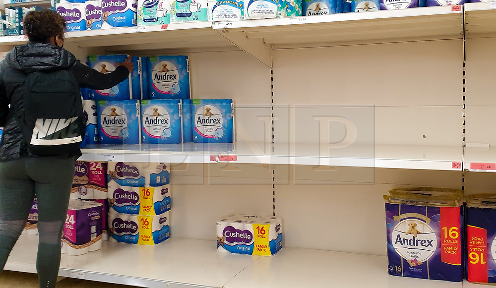 © Licensed to London News Pictures. 28/09/2020. London, UK. A shopper picks a pack of toilet rolls from nearly empty shelves in Sainsbury's supermarket in London as essential items start to run low amidst a possible second lockdown in London due to a rise in COVID-19 cases. The government is considering a 'total social lockdown' for London and parts of the North if coronavirus infection rates do not fall. Number of supermarkets are restricting shoppers from bulk-buying products such as flour, pasta, toilet rolls and anti-bacterial wipes. Photo credit: Dinendra Haria/LNP