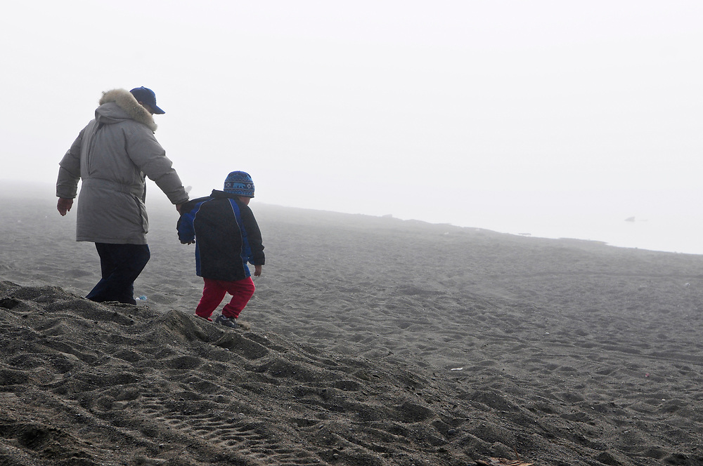 Barrow, Alaska, June 26th, 2008. Father and child playing at the beach by the Arctic Ocean. Summer.