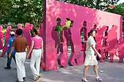 People walk past a piece of public art depicting a cut out in pink of Shanghainese people on Nanjing Road in Shanghai, China.