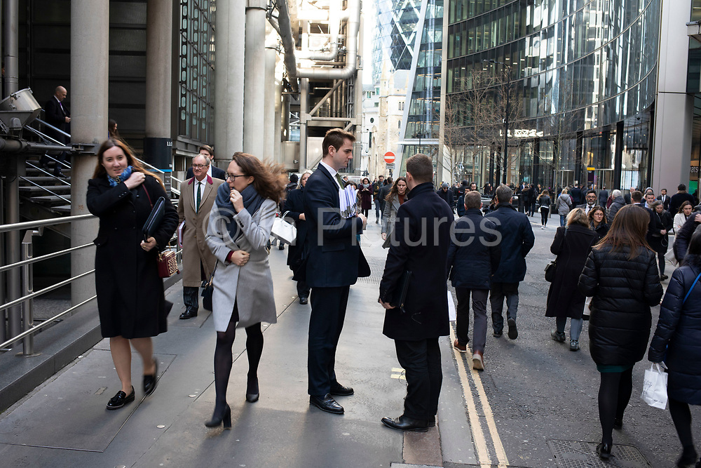 City workers greet each other at a busy lunctime in the City of London on 28th January 2020 in London, England, United Kingdom. The City of London is a historic financial district, home to both the great banking buildings. Modern corporate skyscrapers tower above the vestiges of medieval alleyways below.