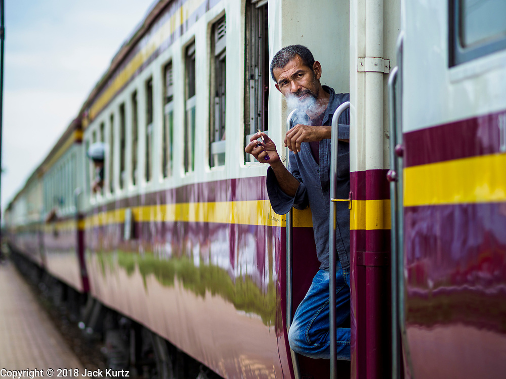 10 JULY 2018 - NAKHON PATHOM, THAILAND:  A man smokes a cigarette while he waits for a train to leave the station in Nakhon Pathom. Nakhon Pathom is about 35 miles west of Bangkok. It is one of the oldest cities in Thailand, archeological evidence suggests there was a settlement on the site of present Nakhon Pathom in the 6th century CE, centuries before the Siamese empires existed. The city is widely considered the first Buddhist community in Thailand and the nearly 400 foot tall Phra Pathom Chedi is considered the first Buddhist temple in Thailand.    PHOTO BY JACK KURTZ