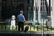 A bald-headed office worker waits next to head sculptures entitled Numen Shifting Votive One & Two by Thomas J Price outside the Leadenhall Building during the 2018 heatwave in the City of London, the capitals financial district, on 24th July 2018, in London, England.