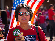 05 OCTOBER 2013 - PHOENIX, ARIZONA:   A woman eats a frozen snack during an immigration march in Phoenix Saturday. More than 1,000 people marched through downtown Phoenix Saturday to demonstrate for the DREAM Act and immigration reform. It was a part of the National Day of Dignity and Respect organized by the Action Network.    PHOTO BY JACK KURTZ
