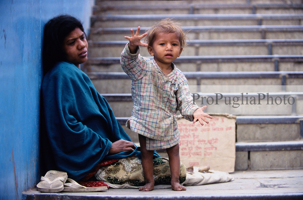 Kathmandu. 20 February 2005.  A mother with her child begging for money