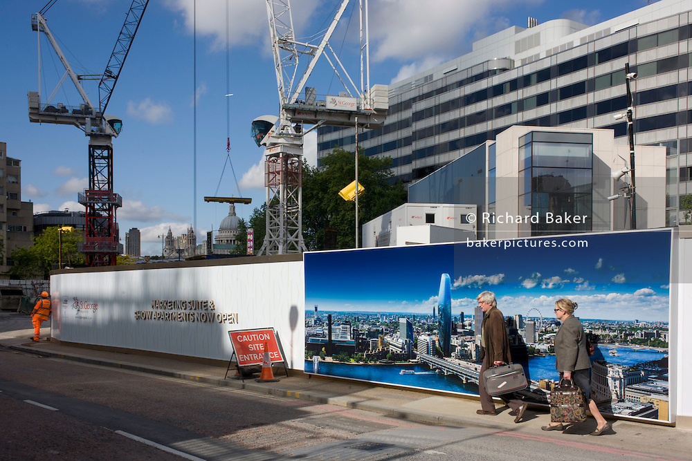 Two travellers walk past a large construction hoarding that shows 1, Blackfriars, a property development marketing suite hoarding landscape. 1 Blackfriars or One Blackfriars, will be a mixed-use development approved for construction at the junction of Blackfriars Road and Stamford Street at Bankside, London. The development make make up a 52-storey tower of a maximum height of 170m and two smaller buildings of 6 and 4 stories respectively. Uses include residential flats, a hotel and retail. In addition a new public space will be created.
