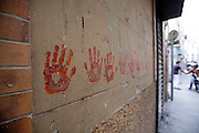 hand prints on the wall with people in the background shaking hands