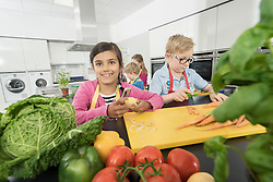 Students peeling and cutting vegetables in home economics class, Bavaria, Germany