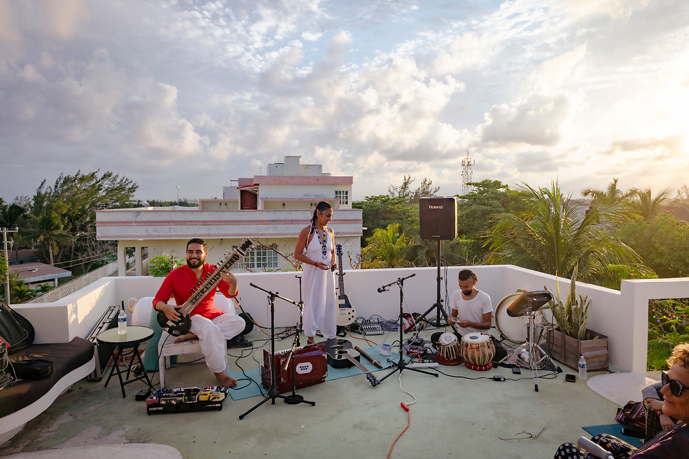 Puerto Morelos, Mexico - May 15, 2021: Musicians on the rooftop at Layla Guesthouse set up to play for a cacao ceremony in Puerto Morelos. Rafa Buitron is on the sitar, Ale Sai on vocals, and Alexei Duran on drums.