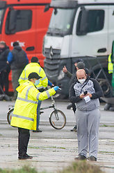 © Licensed to London News Pictures 23/12/2020.        Manston, UK. Medical staff at the airport helping a lorry driver register for a test.The Army and NHS staff have arrived at Manston Airport to administer Covid-19 lateral flow tests to truckers who are stranded in Kent. Angry lorry drivers blockading local roads and clashed with police in Kent this morning. France have closed its borders to all freight traffic because of the new Coronavirus strain. Photo credit:Grant Falvey/LNP