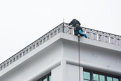 London, UK. 22 January, 2020. A person with climbing equipment prepares to descend from the art deco Carreras Cigarette Factory in Camden. The building, constructed in 1928, is an example of early 20th Century Egyptian Revival architecture.
