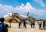 A Vietjet loading in DaLat Airport with passengers walking to the plane. Editorial, March 2, 2018, passengers walking. RAW to Jpg