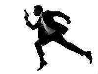 one caucasian man running with handgun in silhouette on white background