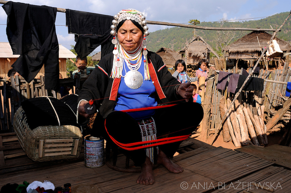 Burma/ Myamnar, nearby Kentung. Akha woman weaving at the terrace of her house in the hilltribe village.