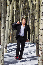 hot man in a suit walking through the snow wearing snowshoes