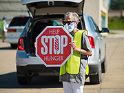 29 MAY 2020 - DES MOINES, IOWA: BARB JAMES, a volunteer, controls the flow of traffic during a produce distribution in a mall parking lot in Des Moines. The Des Moines Area Religious Council (DMARC) and Capitol City Fruit from Norwalk, IA, gave away 1,800 boxes of fresh produce with a mix of vegetables and fruit. The boxes contain enough produce to feed a family of four for a week. The produce was provided by the USDA Farmers to a Families food program. Because of the COVID-19 pandemic, the unemployment rate in Iowa hit 10.2% in May, the highest unemployment rate ever recorded in Iowa and food insecurity in Iowa is impacting communities throughout the state.          PHOTO BY JACK KURTZ