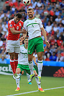 Hal Robson-Kanu of Wales jumps for a header with Gareth McAuley of Northern Ireland.UEFA Euro 2016, last 16 , Wales v Northern Ireland at the Parc des Princes in Paris, France on Saturday 25th June 2016, pic by  Andrew Orchard, Andrew Orchard sports photography.