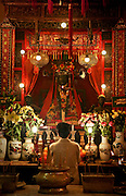 A woman inside a temple in the center of Hong Kong