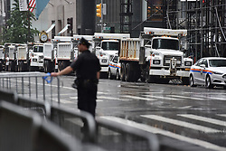 A barricade of New York City Sanitation trucks are parked in front of Trump Tower as an NYPD Police officer directs pedestrian traffic in the rain during President Donald Trump's second day stay in New York City since taking office, New York, NY, on August 15, 2017. (Photo by Anthony Behar)