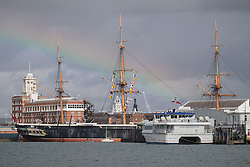 © Licensed to London News Pictures. 30/09/2016. Portsmouth, Hampshire, UK.  A rainbow forms over HMS Warrior and Portsmouth Historic Dockyard, where a 500kg WWII unexploded bomb was discovered during dredging operations yesterday evening. The discovery lead to the evacuation of the Gunwharf Quays leisure complex and surrounding areas. Photo credit: Rob Arnold/LNP