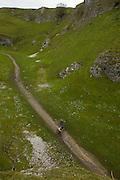 Mountain biking in the deep gorge of Castleton in Cavedale, Derbyshire.